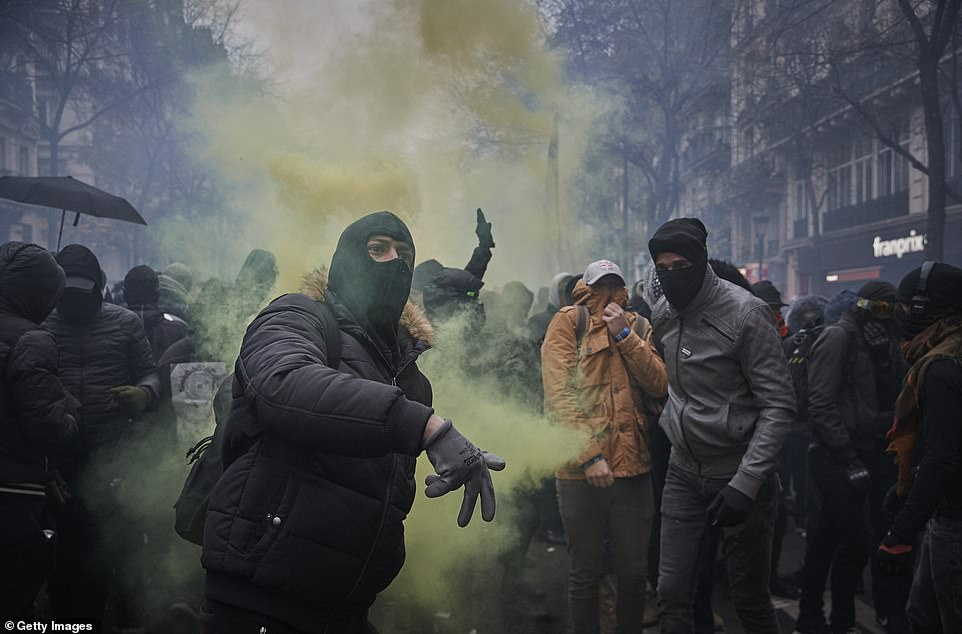 21873500-7759497-A_protester_wearing_a_ski_mask_hurls_a_gas_canister_back_towards-a-129_157557...jpg