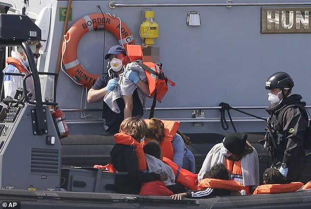 31711244-8609105-A_toddler_pictured_was_carried_to_safety_by_the_Border_Force_as_-a-4_15969838...jpg
