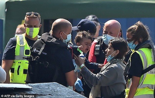 31742170-0-A_mother_is_reunited_with_he_child_as_migrants_believed_to_have_-a-9_1597041260358.jpg