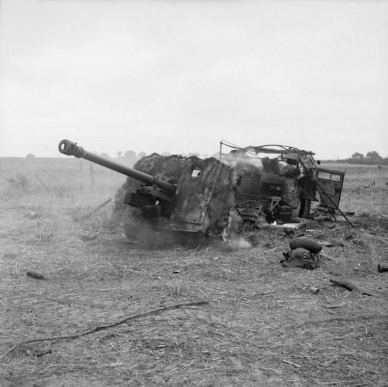 A 17-pdr anti-tank gun and 'Quad' artillery tractor burning on Hill 112 after being hit by mor...jpg