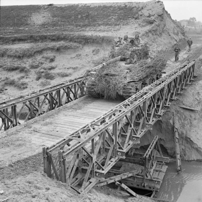 A-heavily-camouflaged-Sherman-tank-crosses-a-Bailey-bridge-over-the-River-Santerno-near-Imola-...jpg