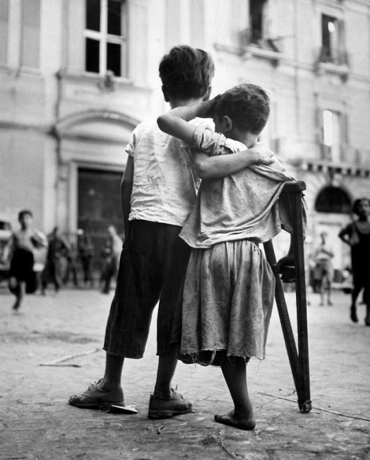 A little Italian boy helps his friend who lost his leg during the Bombing of Naples by Allied ...jpg