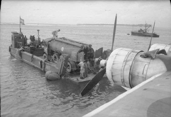 A ramped cargo lighter brings an AEC Matador bowser to a Sunderland flying boat, moored off Di...jpg