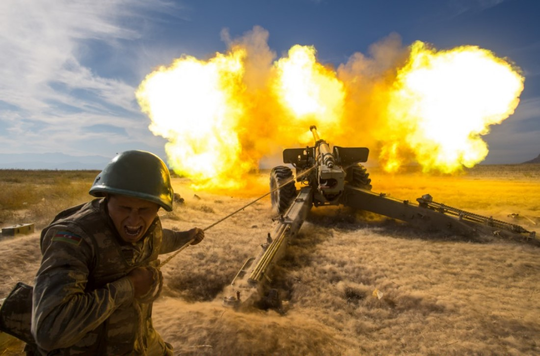 An Azerbaijani soldier fires a howitzer towards Armenian positions as a counter operation con...jpeg