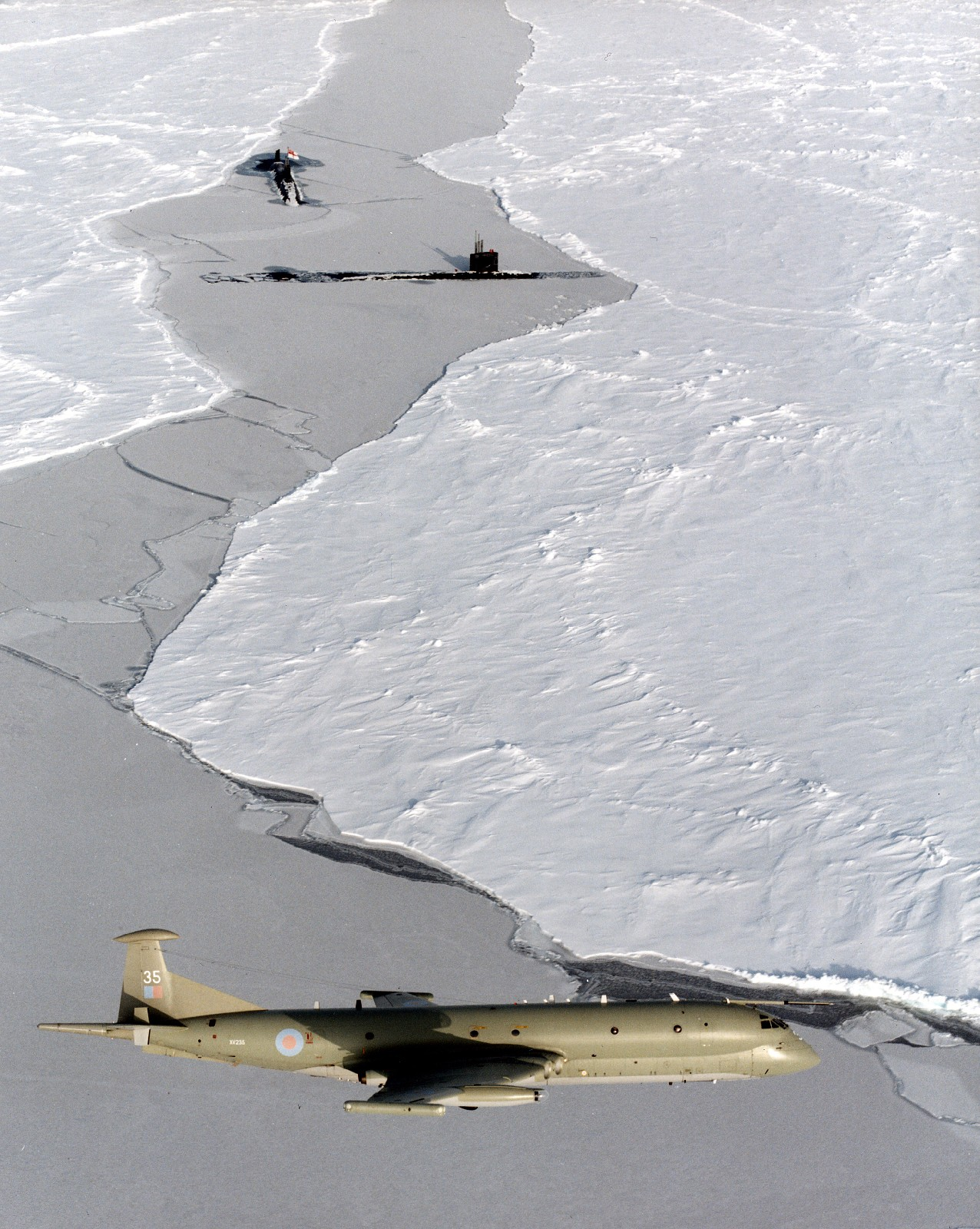 An_RAF_Nimrod_MR2_on_patrol_in_the_skies_over_the_ice,_it_is_shown_with_two_submarines_just_br...jpg