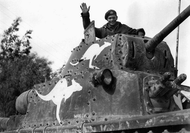 Australian tanker waves from the turret of an Italian M13.40 light tank captured by the 6th Au...jpg