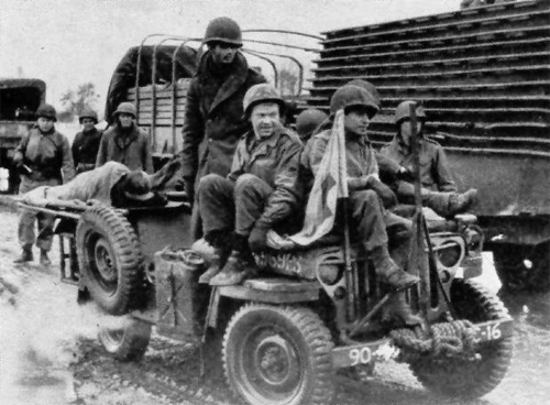 Casualties are being evacuated to the rear by a 90th Infantry Division Jeep Ambulance.png