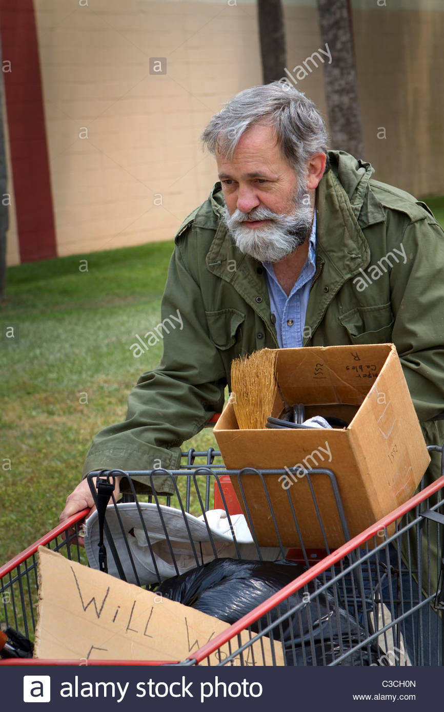 homeless-man-wearing-an-old-army-coat-pushes-a-shopping-cart-holding-C3CH0N.jpg