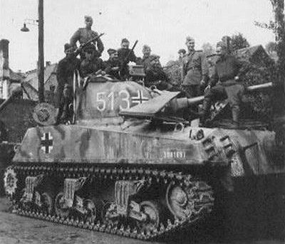 Russian forces pose on a recaptured M4 Sherman that was used by German Panzer forces.jpg