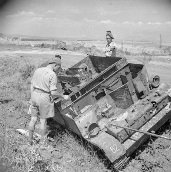 Troops visiting the scene of the Anzio fighting inspect the rusting remains of a Universal Car...jpg